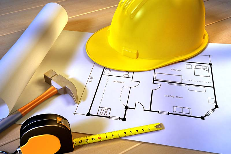 Plans for a new construction phase inspection services under a helmet, hammer and measuring tape