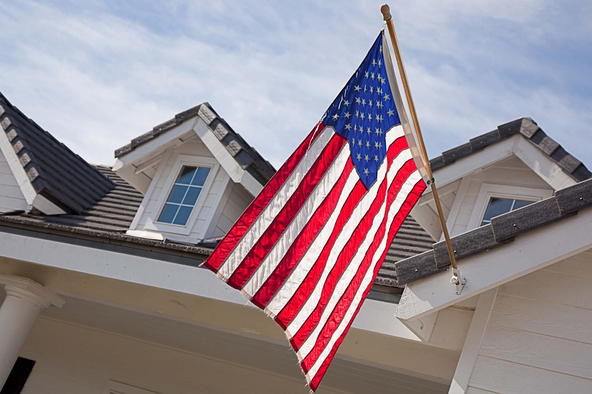 House exterior with an American flag seen while performing home inspection services