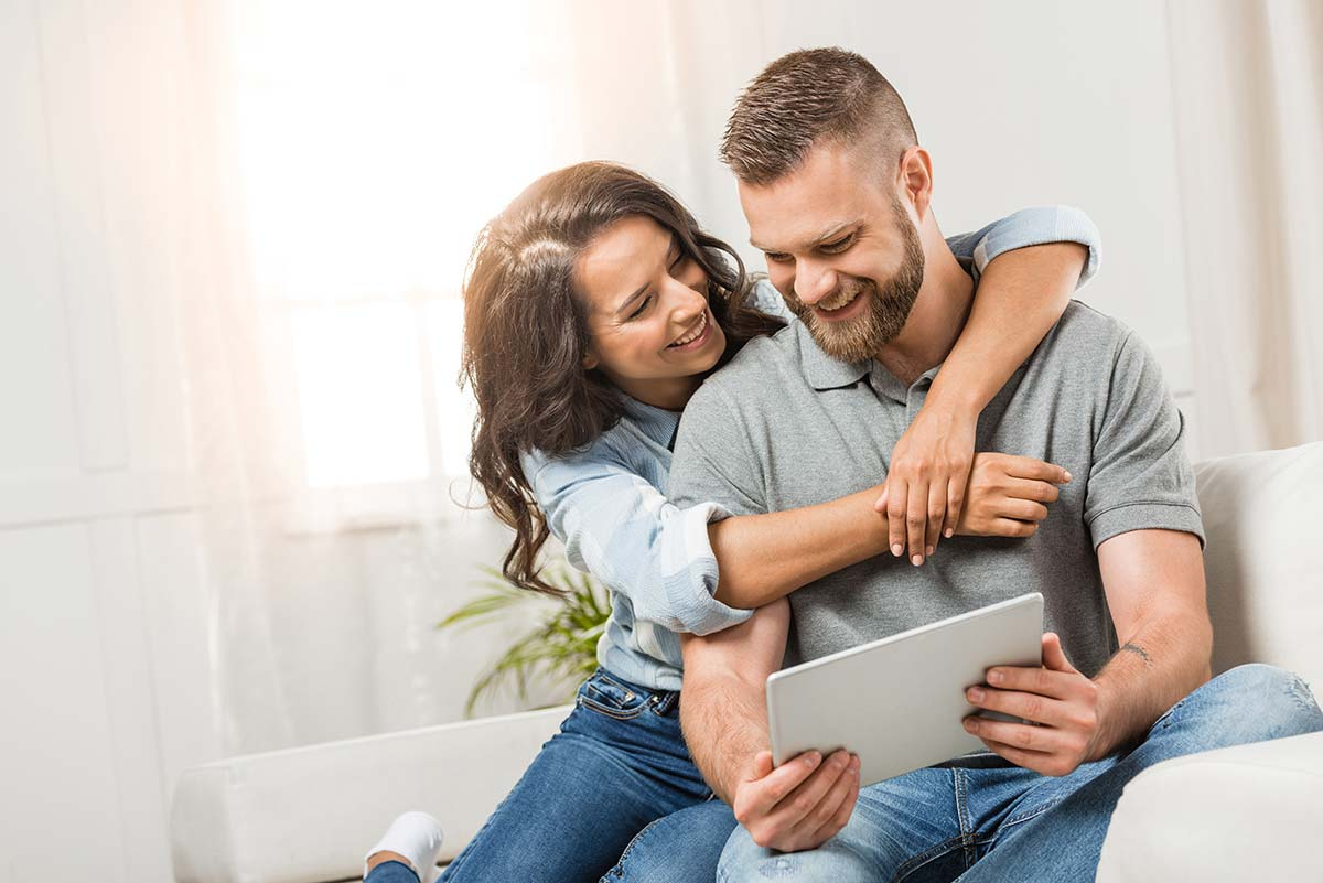 A couple sitting on the couch with a tablet looking at their online home inspection report